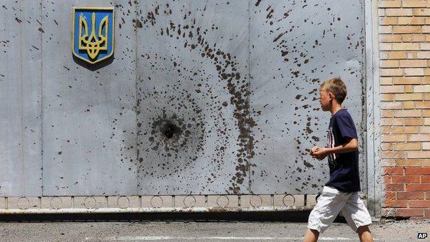 A boy walks past a gate of a Ukrainian military unit in Artyomovsk in the Donetsk region