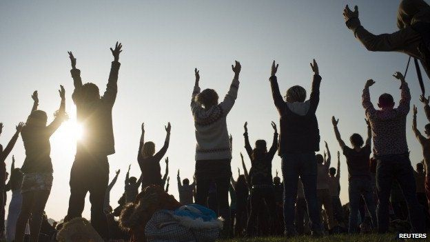 Revellers perform yoga as they celebrate the summer solstice