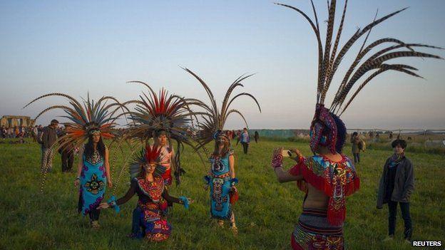 Revellers dressed in Aztec costume celebrate the summer solstice