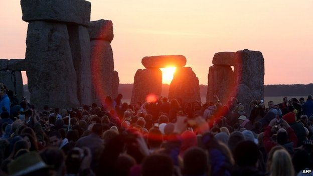 Revellers watch as the sun rises over the standing stones at the prehistoric monument Stonehenge