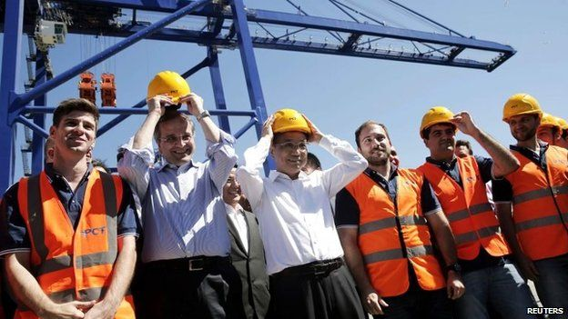 Greek Prime Minister Antonis Samaras (2nd left), and Chinese Premier Li Keqiang (centre) put on helmets as they stand between Greek workers at the port of Piraeus, 20 June 2014