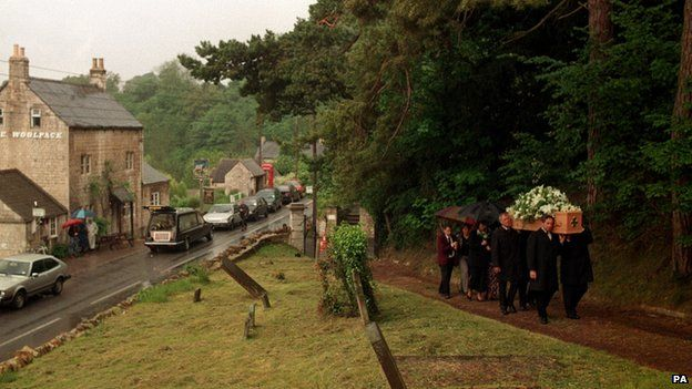 The coffin of author Laurie Lee, most famous for his novel 'Cider With Rosie' is carried to the church past his favourite pub 'The Woolpack' in Slad, Gloucestershire.