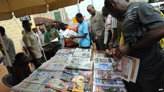 Nigerian reading newspaper headlines in Delta State - April 2011