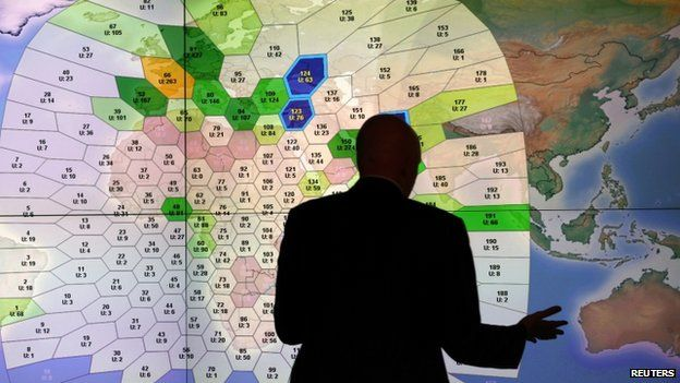 File photo: A member of staff at satellite communications company Inmarsat works in front of a screen showing subscribers using their service throughout the world, at their headquarters in London, 25 March 2014