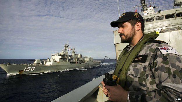 A file handout photo taken on April 7, 2014 and released on April 11 by the Australian Defence shows Able Seaman Maritime Logistics Steward Kirk Scott keeping watch on the forecastle of auxiliary oiler HMAS Success as they conduct a Replenishment at Sea with HMAS Toowoomba whilst both ships are deployed in search of the missing Malaysia Airlines Flight MH370 in the southern Indian Ocean
