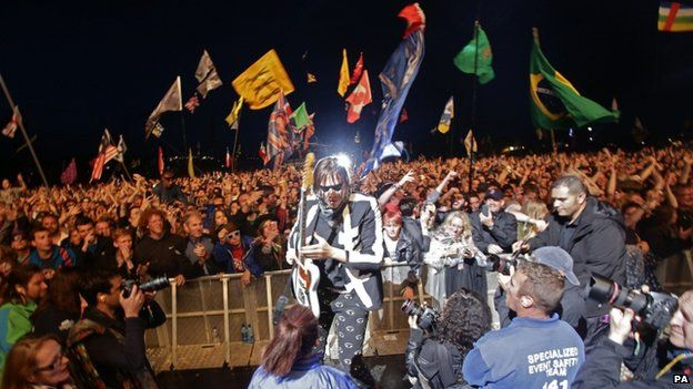 Win Butler of Arcade Fire playing the guitar in front of the stage at Glastonbury
