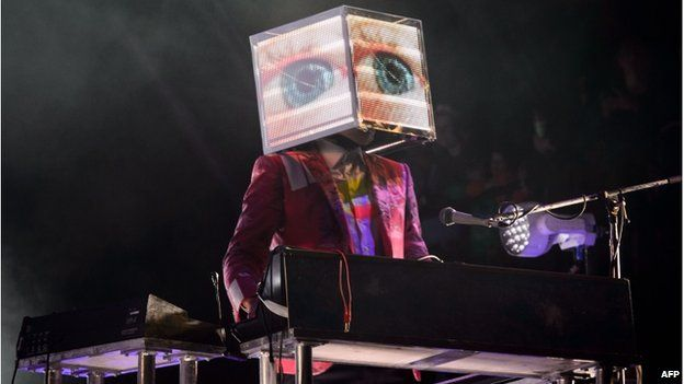 A man with a box on his head playing keyboard for Arcade Fire