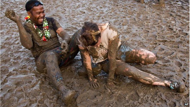 Two people covered in mud at Glastonbury music festival