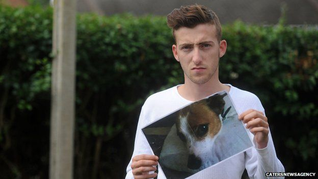 Nicholas Murphy holding a picture of his dog