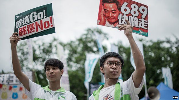 Pro-democracy activists display placards before a pro-democracy rally seeking greater democracy in Hong Kong on 1 July, 2014 as frustration grows over the influence of Beijing on the city