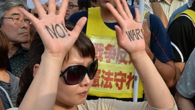 """A protester shows """"No War"""" sign on her palms during a rally in front of the prime minister""""s official residence in Tokyo on July 1, 2014."""