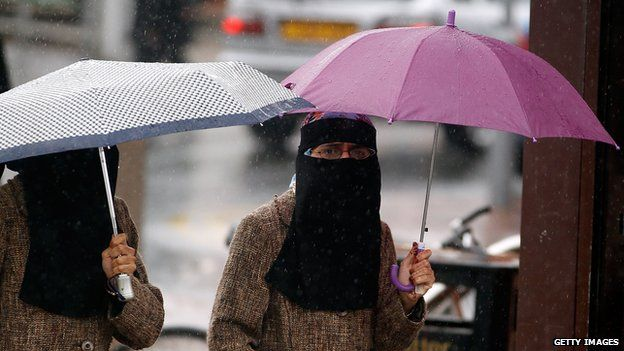 Women, sheltering under umbrellas, wear full face Niqab on the streets of Blackburn on 20 July 2010.