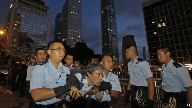 A protester, centre, is taken away by police offices after hundreds of protesters stage a sit-in overnight on a street in the financial district in Hong Kong, 2 July 2014