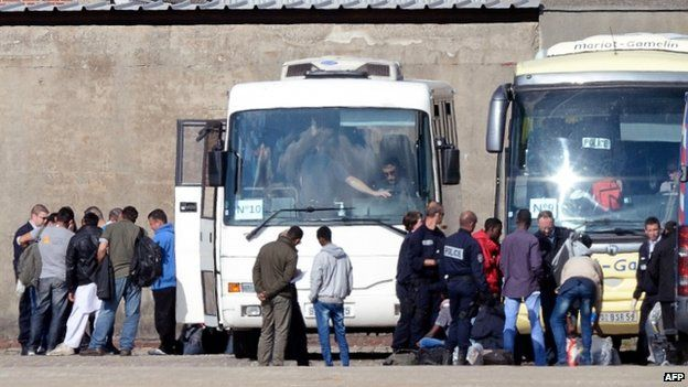 Migrants being put onto a bus after being ejected from their camp in Calais