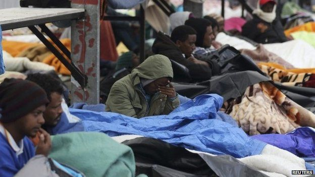 Eritrean migrants rest under blankets in the courtyard at a food distribution centre after they fled their makeshift camp to find shelter in Calais (May 2014)