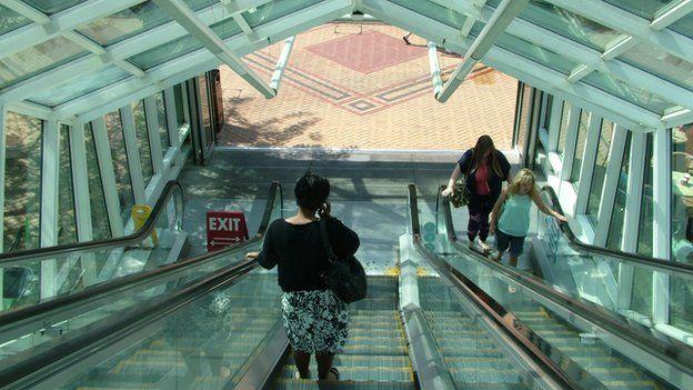 A woman on an escalator