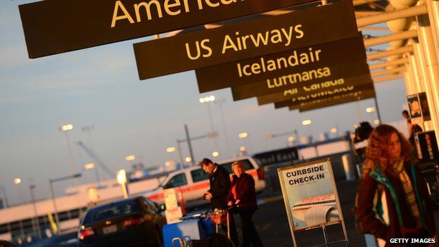 American Airlines and US Airways signs stand next to each others at Denver International Airport in Denver 9 December 2013