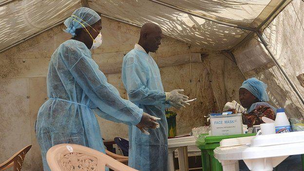 Health workers take blood samples for Ebola virus testing at a screening tent in Kenema, Sierra Leone. 30 June 2014