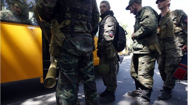 Armed pro-Russian separatists board a bus as they leave their positions in Kramatorsk in eastern Ukraine July 5