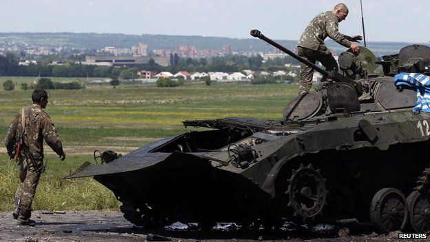 Ukrainian soldiers check a destroyed armoured vehicle at Sloviansk in eastern Ukraine July 5