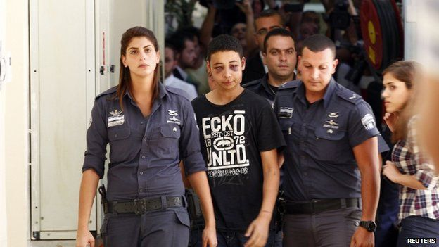 Tariq Khdair (C), is escorted by Israeli prison guards during his appearance at Jerusalem magistrate's court (6 July 2014)