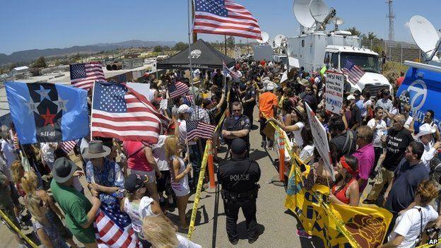 Demonstrators from opposing sides confront each other while being separated by Murrieta police officers, outside a US Border Patrol station in Murrieta, California 4 July 2014