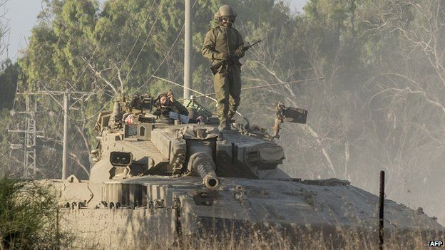 An Israeli soldier stands on his Merkava tank positioned along the southern Israeli border with the Gaza Strip following Israeli air strikes on 10 July 2014