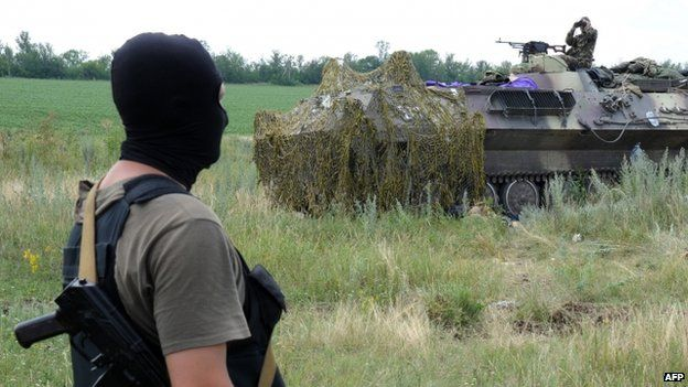 A Ukrainian government soldier stands near an armoured vehicle some 20km south of Donetsk
