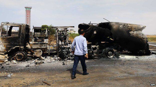 The wreckage of a truck and an airplane are seen at Tripoli international airport in the Libyan capital on July 14