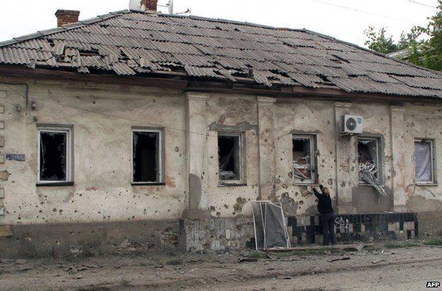 A woman boards up windows in her home in Luhansk after night fighting in the Ukrainian city, 15 July