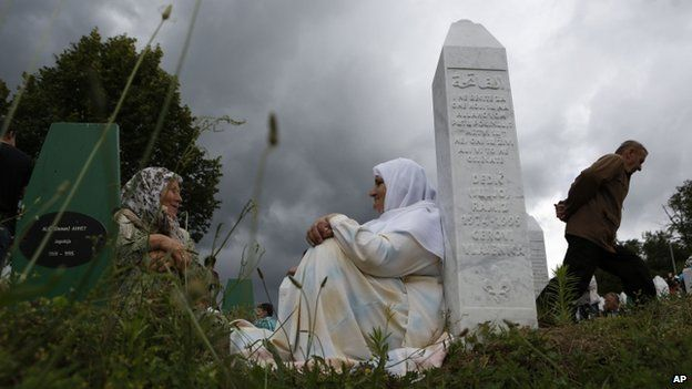 Bosnian Muslim women rest near a gravestone during a funeral in Srebrenica, Bosnia on 11 July 2014.