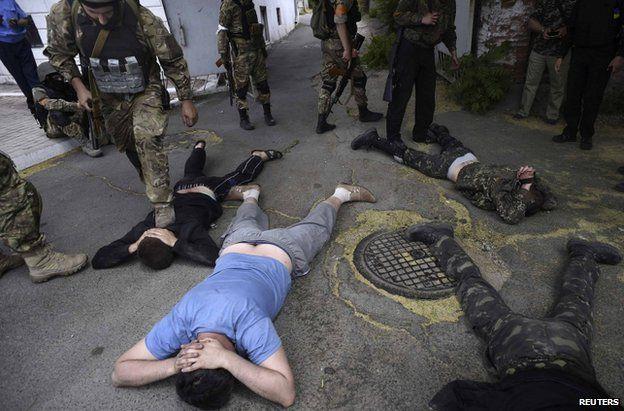 Azov fighters guarding suspected rebels in Mariupol, eastern Ukraine, 13 June