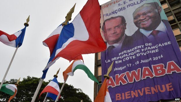 A banner featuring portraits of French President Francois Hollande and President of Ivory Coast Alassane Ouattara is displayed near French and Ivorian national flags in front of the City Hall of Abidjan, Ivory Coast - 16 July 2014