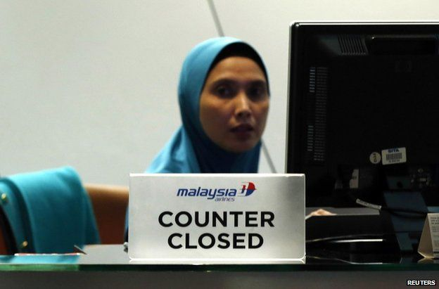A staff member sits behind a closed Malaysia Airlines desk at Kuala Lumpur International Airport, 18 July (local time)