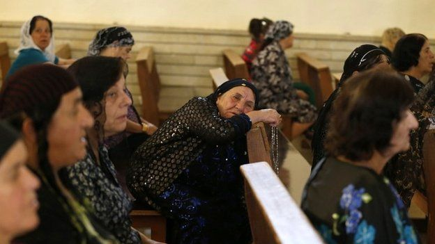 Iraqi women pray at a church outside the northern city of Mosul - 1 July 2014
