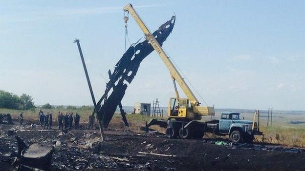 A crane at the crash site lifting large pieces of debris, 20 July 2014