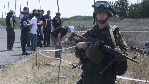 International investigators at the MH17 crash site guarded by an armed rebel in Donetsk, Ukraine (21 July 2014)