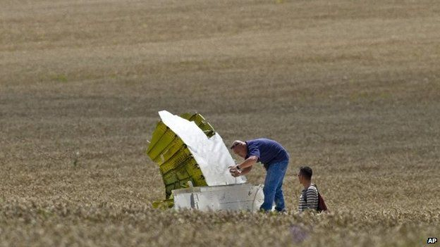 Malaysian air crash investigators take pictures of wreckage at the crash site of Malaysia Airlines Flight 17 near the village of Grabove, eastern Ukraine (22 July 2014)