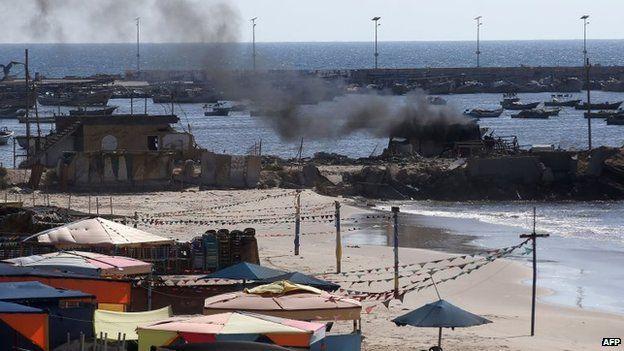 Smoke billows from a beach shack following an Israeli military strike on Gaza City, 16 July 2014
