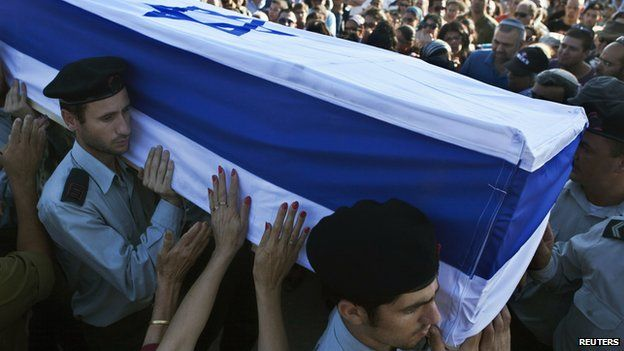 """A mourner touches the flag-draped coffin of Israeli soldier Natan Cohen, killed during fighting in Gaza on Tuesday, during his funeral in Modi""""in, a town between Jerusalem and Tel Aviv, July 23, 2014."""
