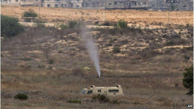 Israeli soldiers spray gas at the exit of a tunnel which was used the day before by Hamas militants to infiltrate Israeli lines, on July 22,