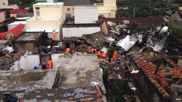 Police and soldiers guard the crash site of the TransAsia Airways plane on the Penghu Islands in the Taiwan Strait on 24 July 2014