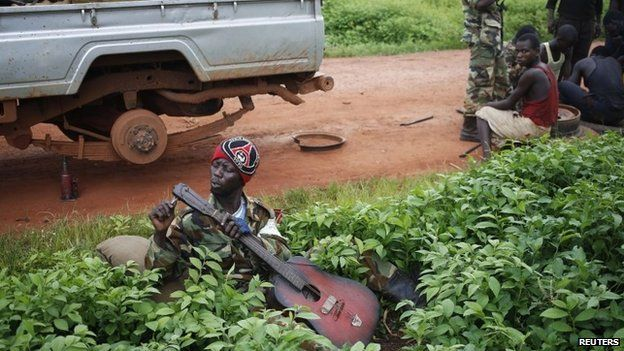 A Seleka fighter adjusts a broken guitar in a village between Bambari and Grimari in CAR on 31 May 2014