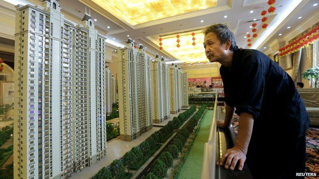 A man looking at a model of a new apartment complex in Wuhan