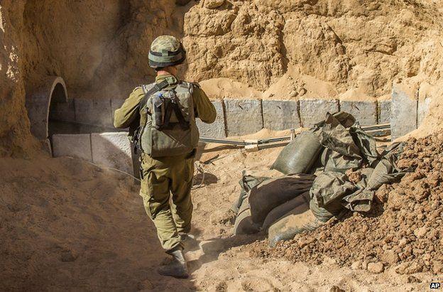 An Israeli officer walks by a tunnel on the Gaza-Israeli border which was allegedly dug by militants to launch attacks on Israel, 25 July