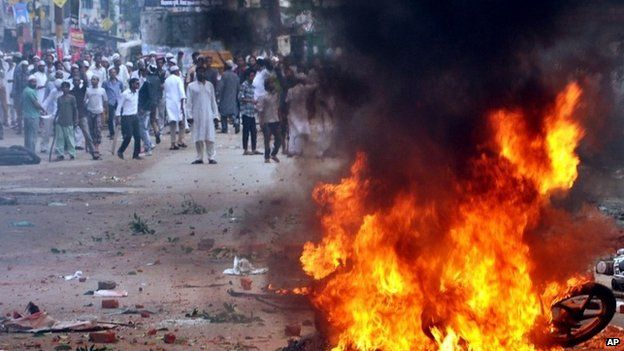 Indians stand near a burning motorcycle, set on fire during a protest between two communities in Saharanpur district of Uttar Pradesh state, India, Saturday, July 26, 2014