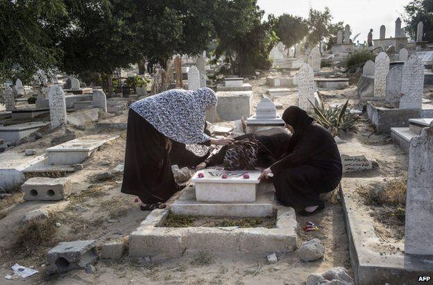 Palestinian women visit a grave in Gaza, 28 July