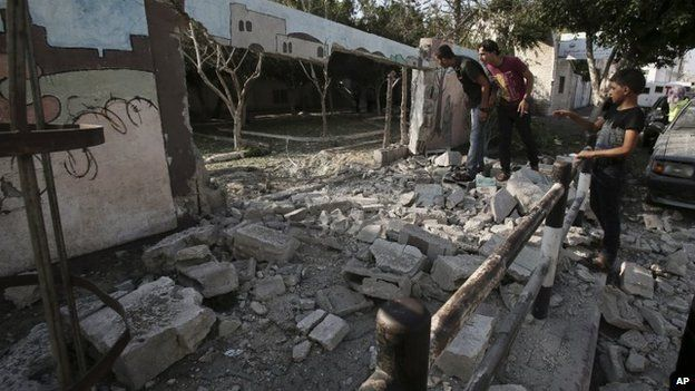 Palestinians inspect the destroyed wall of Shifa hospital after an air strike, in Gaza, in the northern Gaza Strip, 28 July 2014