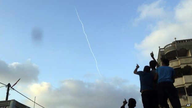 Palestinians watch the smoke trail of a missile fired by Palestinian militants from inside northern Gaza Strip, 28 July 2014