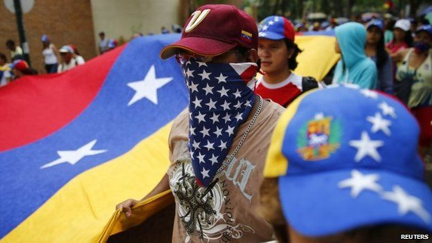 An anti-government protester covers his face with a US flag during a protest march in Caracas on 10 May, 2014